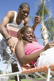 Young Couple On Vacation. Portrait of a young African American women relaxing on deck chair with men standing behind chair Stock Photography