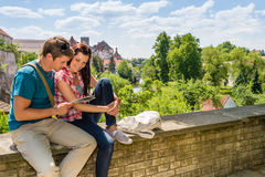 Young couple on vacation looking at map. Young happy couple on vacation in city looking at map Royalty Free Stock Image