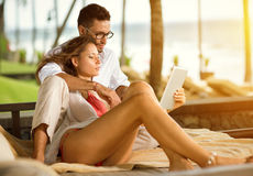Young couple on vacation with tablet pc. Young couple lying on sunbed in tropical garden and using tablet pc Stock Images