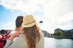 Young couple on vacation taking a selfie. As they stand overlooking a waterfront town, view from behind looking towards the mobile phone on the end of the stick Stock Image