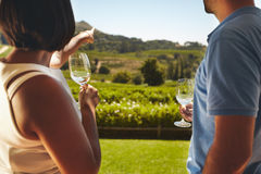 Young couple on vacation at vineyard. Young couple on vacation holding a glass of wine, with women pointing away at vineyard, showing something to her boyfriend Stock Photography