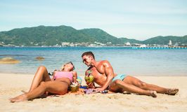 Young couple vacationer having genuine fun on tropical Phuket be. Ach in Thailand with coconut drink - Active youth love and travel concept around world Stock Image