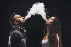 Young couple vaping e-cigarette with smoke on black closeup Stock Image