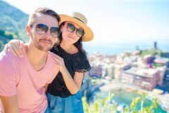 Young couple with view of the old coastal village in Cinque Terre national park, Liguria, Italy ,Europe. Young couple with view of the old coastal village royalty free stock photos
