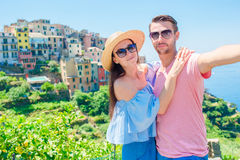 Young couple with view of the old coastal village background of Corniglia, Cinque Terre national park, Liguria, Italy. Young couple with view of the old coastal stock image