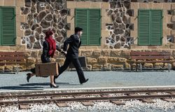 Young couple with vintage suitcase on the trainlines ready for a. Young couple with vintage suitcase running fast outside a train station to catch the last train Stock Images
