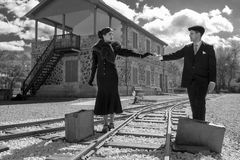 Young couple with vintage suitcase on the trainlines ready for a. Young couple with vintage suitcase walking on the trainlines ready for a journey Stock Photo