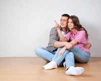 Young couple visualizing the decor of their new home sitting on the bare wooden floor pointing out and discussing placement of fur Stock Photo