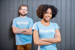 Young couple of volunteers. Portrait of an happy multi ethnic volunteers in blue t-shirts standing indoors on the gray wall background Stock Image