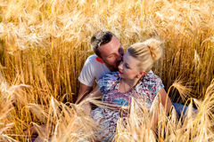 Young couple waiting for a baby. Happy and young pregnant couple hugging in nature Royalty Free Stock Photo