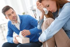 Young couple waiting for psychology session family problems girl crying. Young couple men and women waiting for psychology session sitting on sofa girl crying Stock Photography