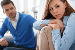 Young couple waiting for psychology session family problems girl looking aside sad. Young couple men and women waiting for psychology session sitting on sofa stock photography