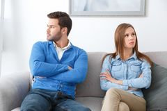 Young couple waiting for psychology session family problems looking diffrent side. Young couple men and women waiting for psychology session sitting on sofa stock images