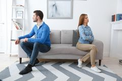 Young couple waiting for psychology session family problems turning aside from each other. Young couple men and women waiting for psychology session sitting on Royalty Free Stock Photos