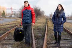 Young couple waiting on the railway tracks Stock Photos