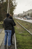 Young couple waiting for a tram on stop. Young couple waiting for a train in a raining day on transport stop royalty free stock image
