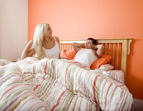 Young Couple Waking Up in Bed. Young couple wake up in bed under a striped bedspread. Horizontal shot Royalty Free Stock Photography