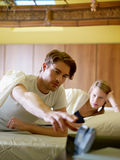 Young couple waking up in the morning. Caucasian heterosexual couple in bed snoozing alarm clock. Vertical shape, front view, waist up Stock Photography