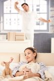 Young couple waking up in the morning together. Young couple waking up in the morning, woman drinking tea, man stretching in the background Royalty Free Stock Photo