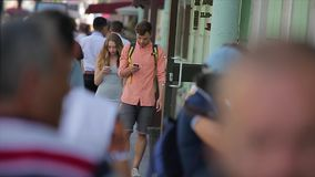 Young couple walk along the busy city street and look at their smartphones in slow motion