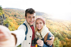 Young couple on a walk in autumn forest taking selfie Stock Image