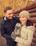 Girl and guy with cat in autumn park. Young couple on walk in autumn park with cat stock photography