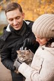 Young girl and guy with cat in autumn park. Young couple on walk in autumn park with cat stock photo
