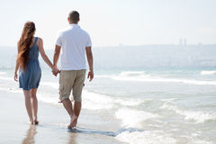 Young couple walk at the beach. Happy young couple walk at the beach stock photography