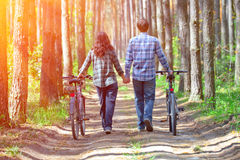 Young couple walk with bicycles Stock Image