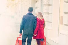 Young couple walk in city, celebrating Valentines Day holding sh. Young couple celebrating Valentines Day. They are holding each other hands and waling on street royalty free stock images