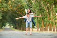 Young couple walk on country road with high trees, romantic people concept, summer season Royalty Free Stock Photo