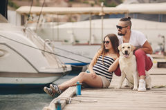 Young couple on a walk in the Harbor with a dog Royalty Free Stock Photos