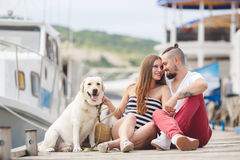 Young couple on a walk in the Harbor with a dog Stock Photos