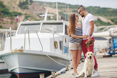 Young couple on a walk in the Harbor with a dog Stock Image
