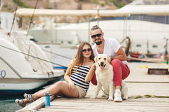 Young couple on a walk in the Harbor with a dog Royalty Free Stock Photography
