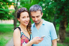 Young couple on a walk with their smart phones Royalty Free Stock Photos