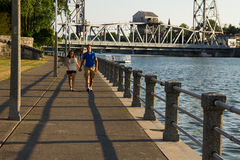 Young Couple Walking. A young couple walking along a boardwalk with bridge in background Stock Images