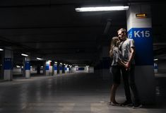 Young couple walking across the parking garage stock images