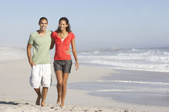 Young Couple Walking Along Beach Stock Image