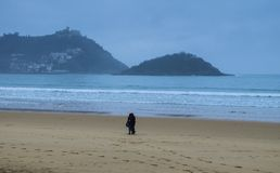 Young couple walking along the beach in the city of Donostia Stock Photos