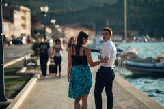 Young couple walking along the coastal lane in sunset.Man turning to see another woman,seeing ex girlfriend.Turning on and looking. Back over his shoulder Royalty Free Stock Photo
