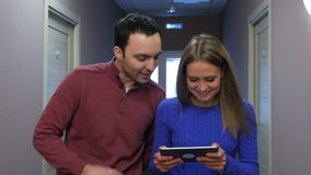 Young couple walking along hotel hall with smiling woman holding tablet. Professional shot in 4K resolution. 073. You can use it e.g. in your commercial video stock footage