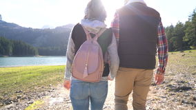 Young couple walking along the lake. At sunset stock video footage