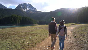 Young couple walking along the lake. At sunset stock footage