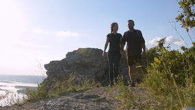 Young couple walking along a mountain path. The man points up on the left edge of the screen. Against the background of the top of stock video footage