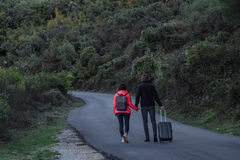Young couple walking along the road with a suitcase Stock Images