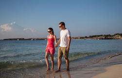 Young couple walking along the seashore Stock Images