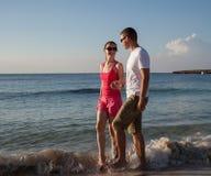 Young couple walking along the seashore Stock Photography
