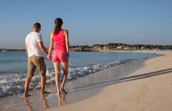 Young couple walking along the seashore Royalty Free Stock Image