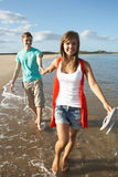 Young Couple Walking Along Shoreline. Romantic Young Couple Walking Along Shoreline Of Beach Holding Hands Stock Image